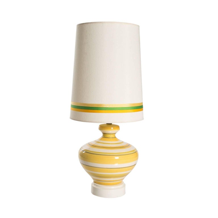 Pair of glazed ceramic yellow, white, and green striped table lamps with matching green and yellow shades.