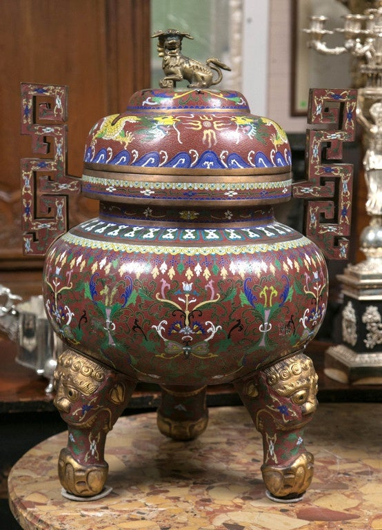 This urn is topped with a foo dog finial. The ground color is deep red/brown. Two yellow dragons encircle the top. Bright and muted  multi colored symbols decorate the body. Gilt stylized faces decorate the three feet.  Width posted includes the