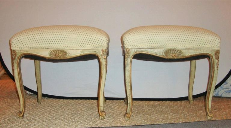 An elegant pair of French carved and painted stools, with gilt accents throughout.