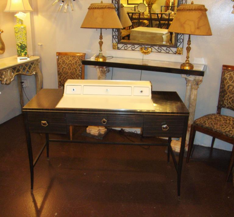 Jonathan Charles Hollywood Regency leather and Macassar desk or vanity. A stylish and fancy desk or vanity by this fine designer. The chrome capped sabots and drawer pulls hi light this Macassar wood desk having Art Deco flair with leather writing