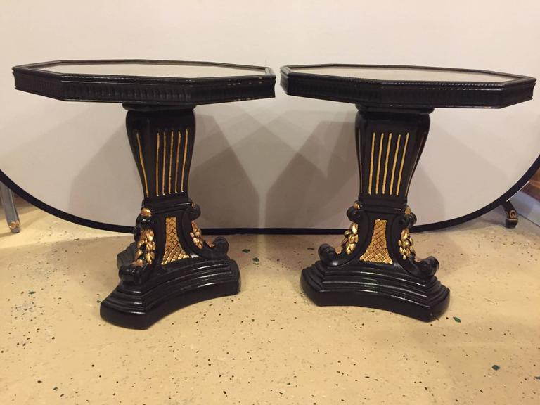 Pair of gilt glass top ebonized and gilt decorated end or side tables. These fine Hollywood Regency side or end tables would surely compliment any area of the home.
