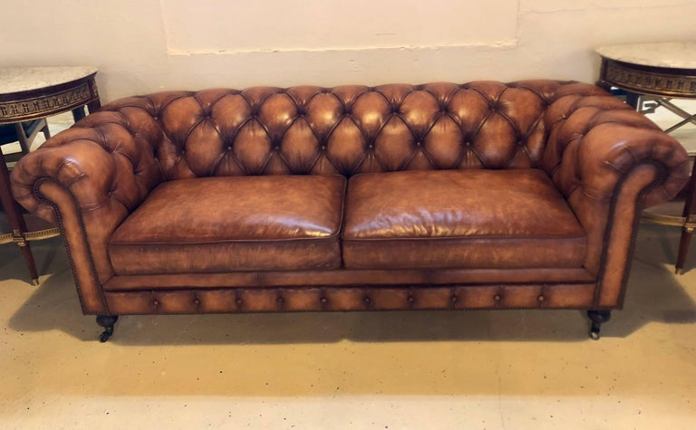 An English worn leather Chesterfield sofa. Supported by bun feet on brass casters stands this very comfortable sofa in a fine worn leather.