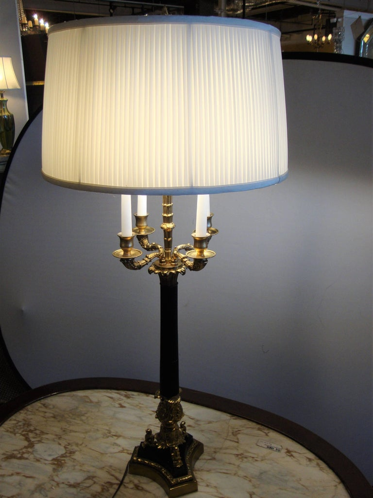 Pair of bronze neoclassical style table lamps. Each taking two 60 watt bulbs. The bronze base and Corinthian column support a four arm candleholder. Each having custom shades that can be used or discarded.