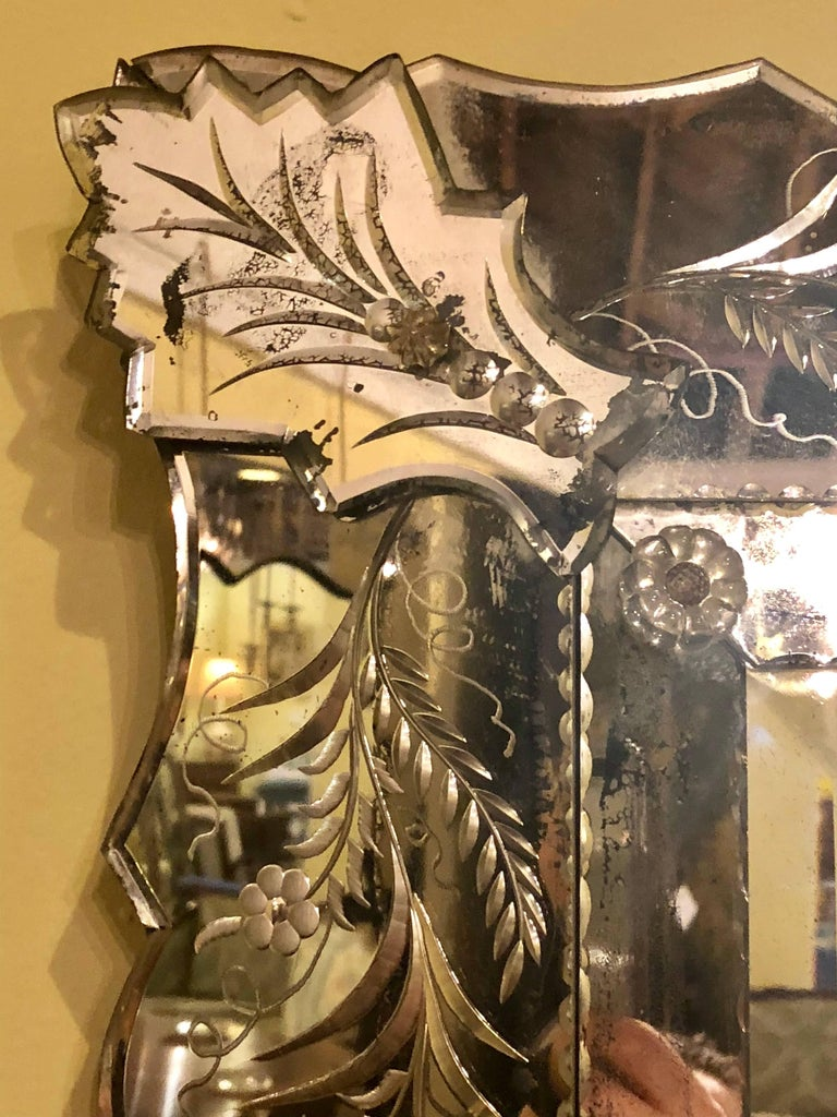 An Antique Venetian etched glass wall or console mirror. The centre bevelled mirror with in thin cut mirror frame sitting inside of a much thicker etched glass frame. One corner floral with a crack as photographed.