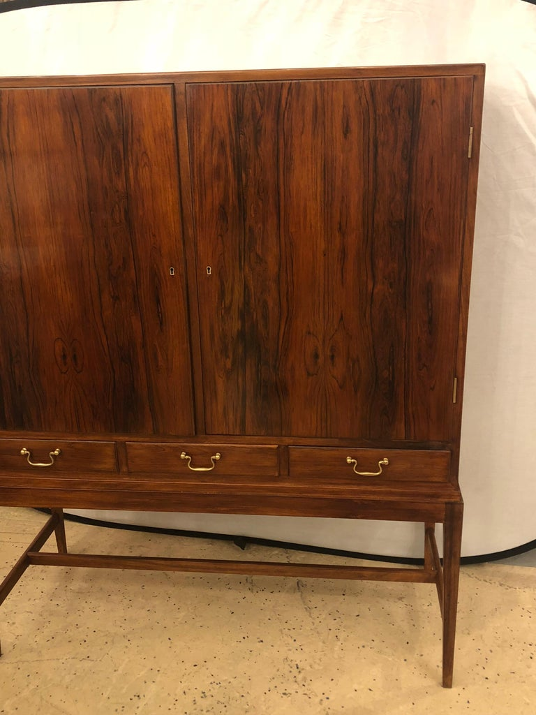 A two-door Over three-drawer Mid-Century Modern Brazilian rosewood cabinet. Recently hand rubbed French polished. This sleek and stylish cabinet has long lean tapering solid rosewood legs with a stretcher supporting a solid rosewood cabinet of two