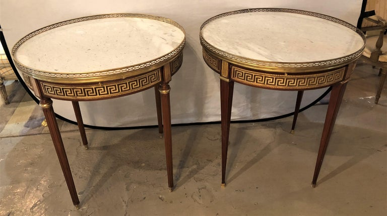 A pair of marble-top Greek key Bouillotte or end tables in mahogany with double drawers and pull-out slides. Each bronze sabot leading to a group of tapering legs terminating in bronze capitals supporting a apron have full Greek key design and