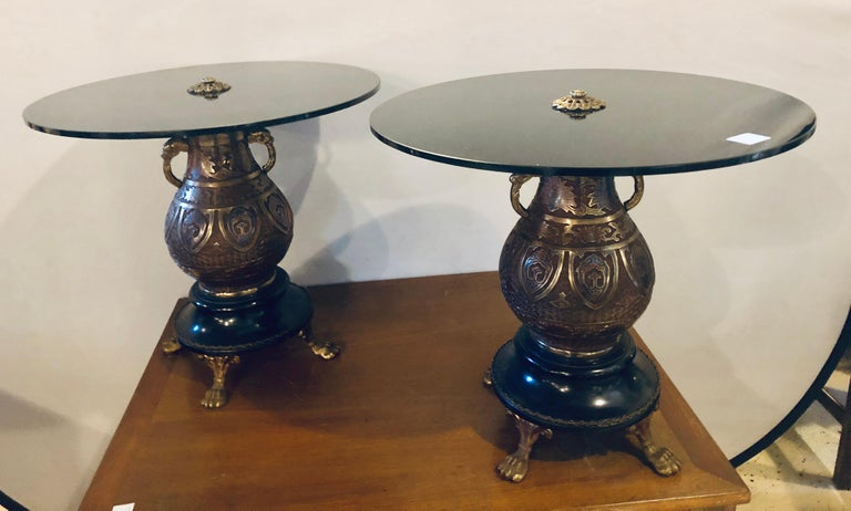 A pair of bronze urn form glass top end tables. Each Chinese inspired end table has a chinoiserie urn on a marble base and bronze feet supporting a black glass circular table top. Sitting side by side these make a lovely coffee table.