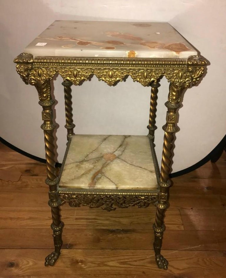 A two-tier bronze and alabaster pedestal or end table. This fine pedestal table is wonderfully case in bronze with alabaster shelves.
