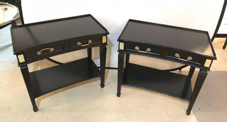 Pair of Hollywood Regency Jansen Style ebonized one drawer end tables or bedside stands. Each having oak secondary and an ebony finish with bronze mounts and framed tops.