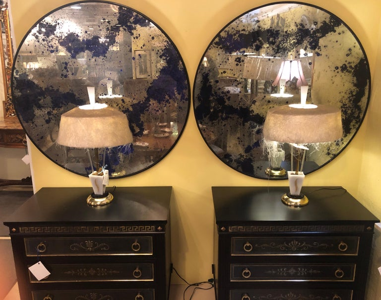 A fine custom pair of monumental Art Deco circular black and silver gilt distressed wall or console mirrors that can be used as table tops for any center or end tables. Each large and impressive mirrored frame highly distressed and speckled in ebony