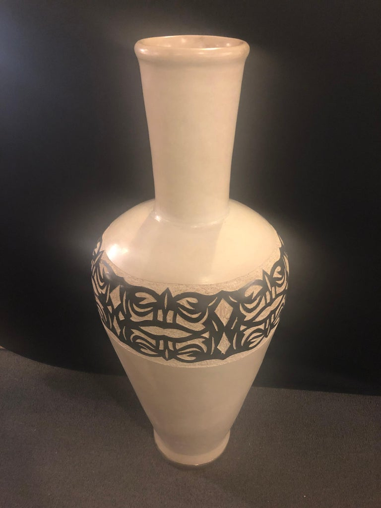 A beautiful vintage handmade pottery floor vase. The vase features an elegant earthy off-white natural color with decorative motifs hand painted by master artisans in the Atlas Mountains in Morocco.