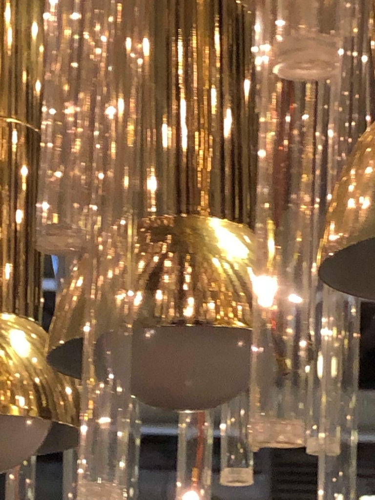 A stunning modern three-light chandelier flush mount separate switch for three bulbs having a myraid of Lucite lighted prisms. The chandelier features a rectangular brass flush mount apron and symmetrically gathered Lucite pieces that create a