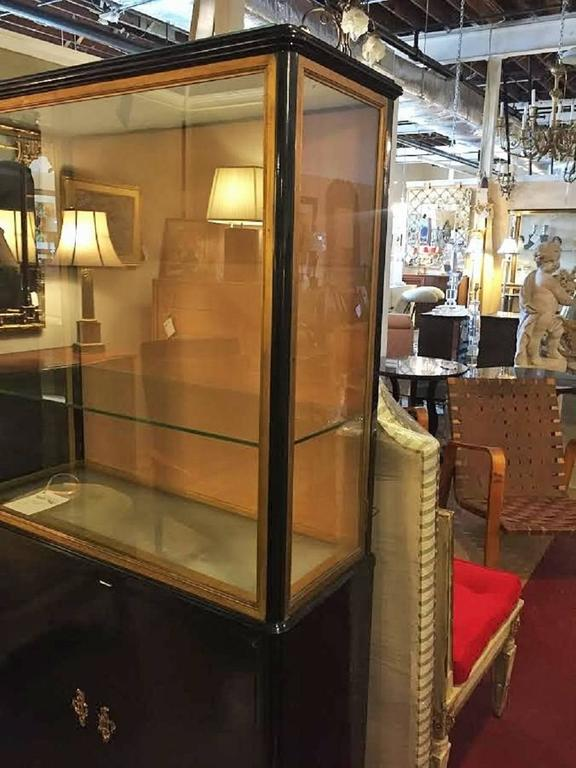 Hollywood Regency at its finest. Ebonized Louis XV Style China cabinet vitrine bookcase in the style of Maison Jansen. This bonze mounted bookcase or vitrine has a lower double door case supporting a vitrine shelved cabinet. The top appears to be