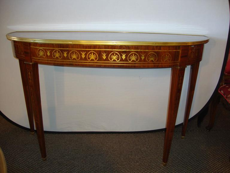 Finest Boulle inlaid demilune console. This recently polished, demilune console table with all-over boulle (brass) inlays. The tapering Louis XVI stylized legs with floral inlays supporting an apron of Fine brass inlays leading to a wonderful
