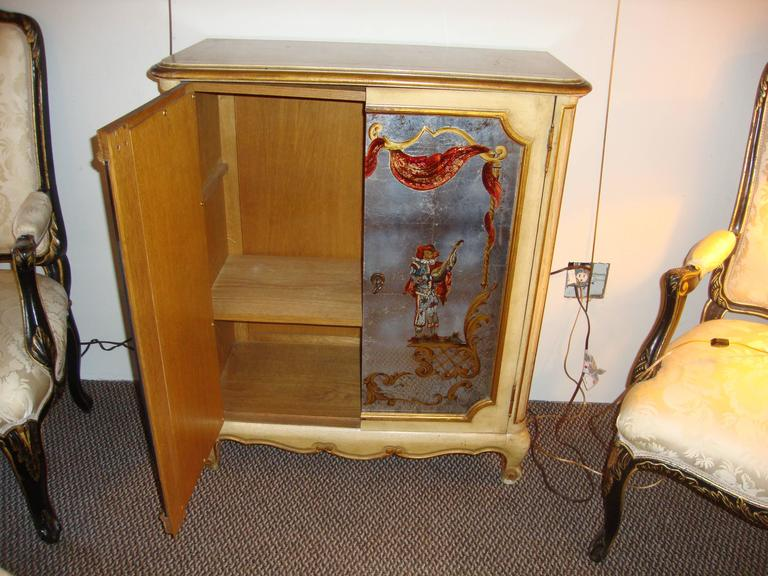 A French Maison Jansen églomisé and painted cabinet commode. A fine Louis XV style cabinet by this highly sought after designer. The églomisé mirrored front doors having opposing figures playing musical instruments. The case itself of oak