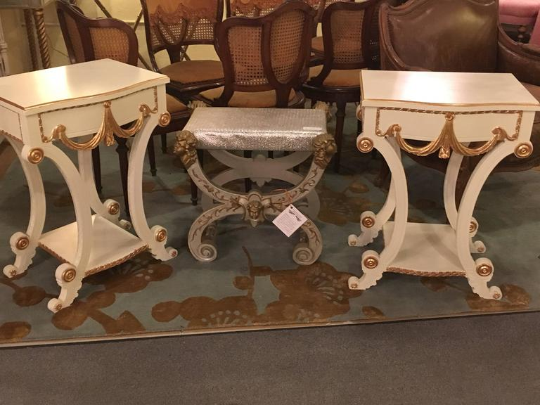 Pair of Grosfeld House Hollywood Regency paint and gilt decorated end tables or nightstands. This wonderfully decorative pair of end tables have been professionally redone in a Lancaster white finish with hand applied gilt gold high lights. Standing