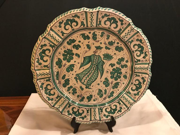 An Italian paint decorated platter. The back having a fire drilled pair of holds to mount this decorative platter to a wall. The platter itself marked Italy. The scalloped edges framing a white and green jester with flowing fruit and flowers in a