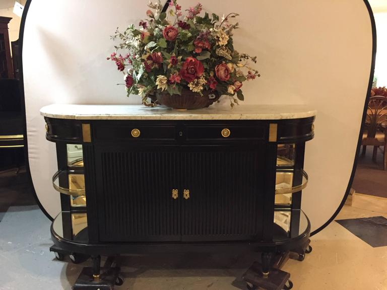 Hollywood Regency at its very finest. This sleek and stylish Monumental Louis XVI style sideboard with vitrine sides by Maison Jansen is nothing short of spectacular. The short stout feet with bronze sabots leading to a mammoth double door ebony