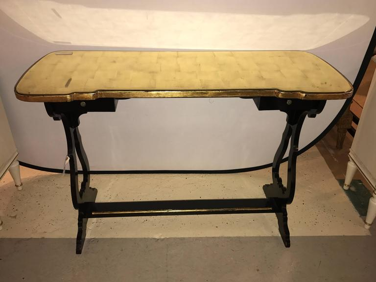 French ebonized console table or desk with gilt glass top Jansen style. Bringing Hollywood Regency to the forefront comes this finely ebonized desk in the fashion of the iconic Maison Jansen. The ebonized and gilt gold base having a lower shelf with