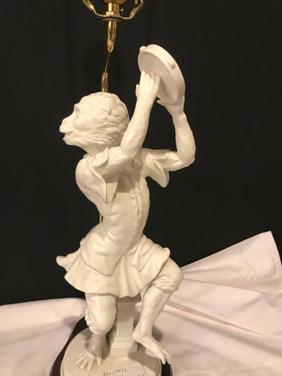 Pair of white porcelain opposing monkey lamps. A wonderful playful pair of monkeys one having a tambourine and the other playing a flute both in formal garb of the time. Each apparently sitting on a pedestal and playing for the crowd. Finely