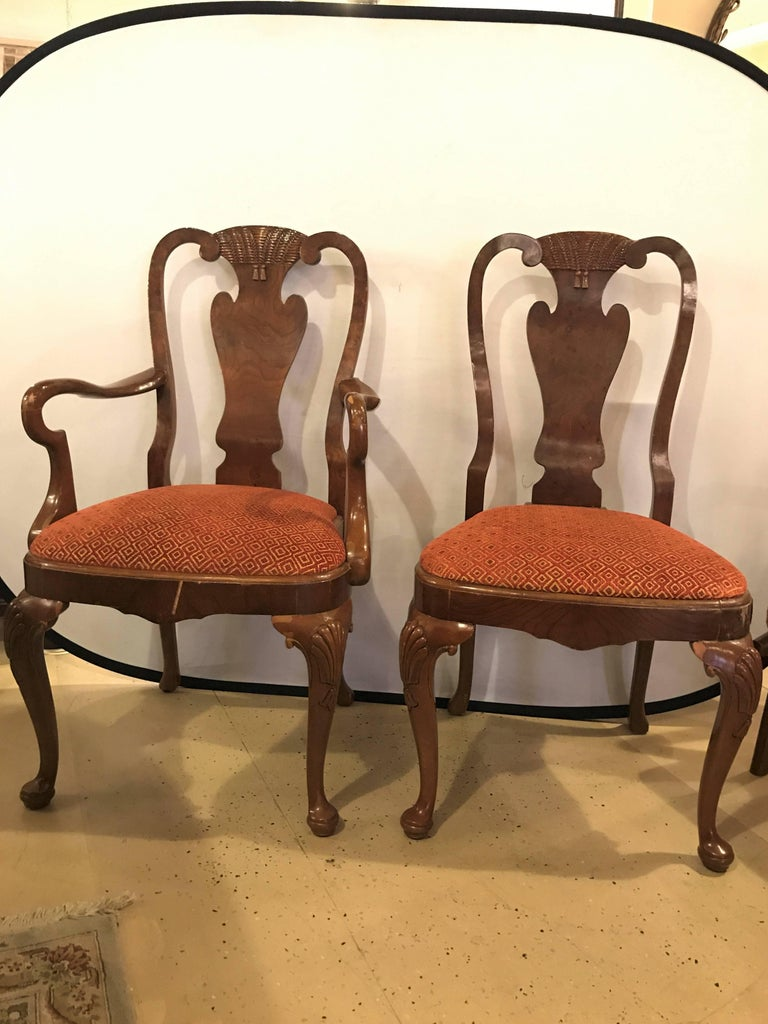 Set of ten Queen Anne style dining room chairs. A pair of arm and eight side chairs comprise this fine custom quality set of chairs. Each in a rich burl wood frame with carved turned feet leading to cabriole legs. The thick solid apron supporting an