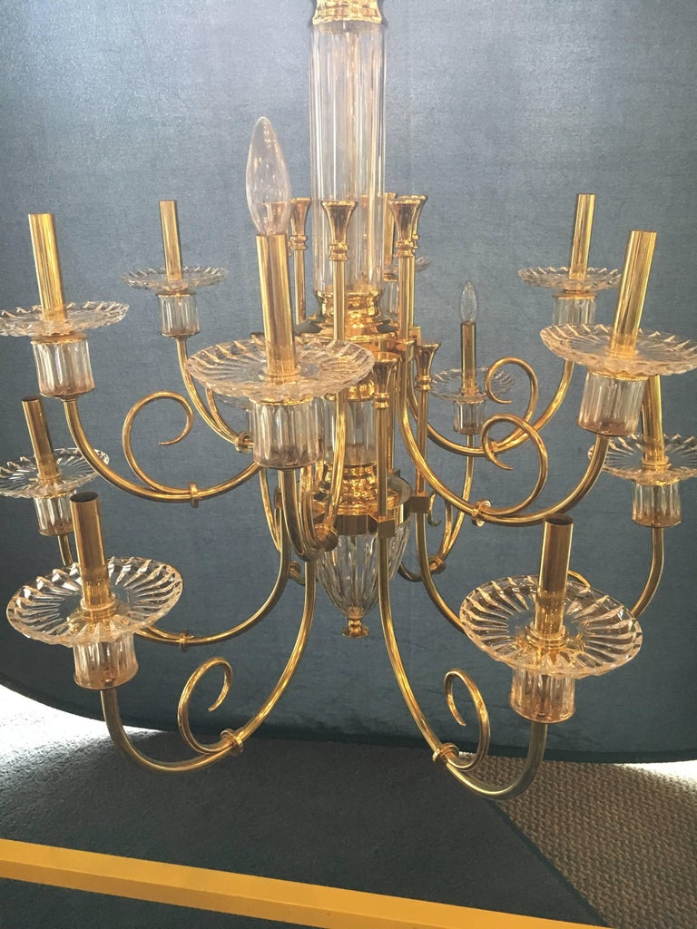 Custom quality at its finest. This highly decorative 12-light bronze and cut crystal chandelier with chain and crystal canopy are sure to light up any room. In a word this Hollywood Regency style chandelier is too sweet. The crystal and bronze