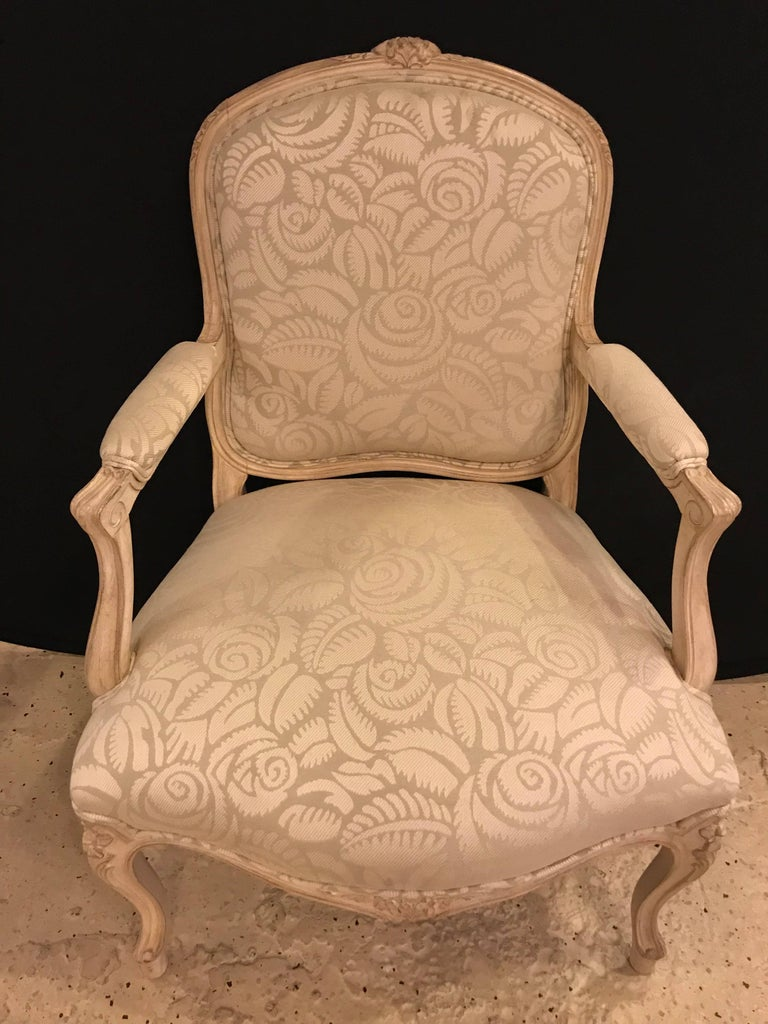 A pair of Louis XV style bergère armchairs. Each having a finely carved frame and clean floral pattern fabric with carved rosettes throughout.