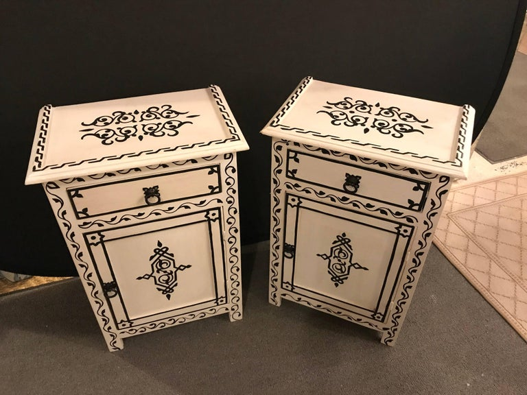 A pair of hand-painted Moroccan nightstands or end tables. Hand-painted by master artisans, this stunning pair of Moroccan nightstands features lattice work and impresses with its unique design and a welcoming black and white color.