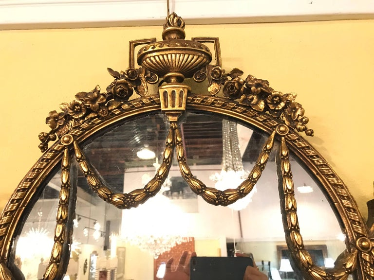 Pair of George III style giltwood and composite shelved wall / console mirrors. One of a kind finely detailed and sizable are these long shelved wonderfully carved wall or console mirrors. The top adorning a large urn having flowing roses, vines and