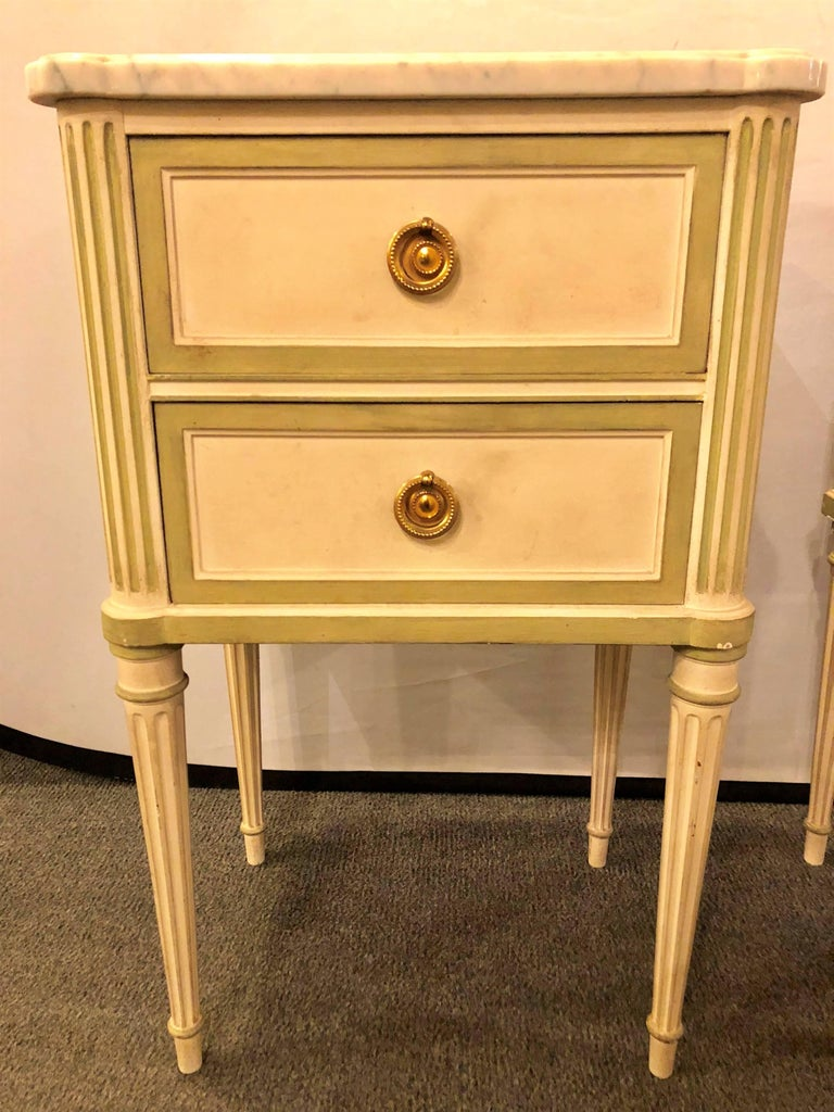 Pair of Louis XVI style paint decorated marble top end tables or nightstands. This pair of custom quality distressed and aged stands each having a white marble top on an olive green decorated frame with a linen white background. Having two drawers