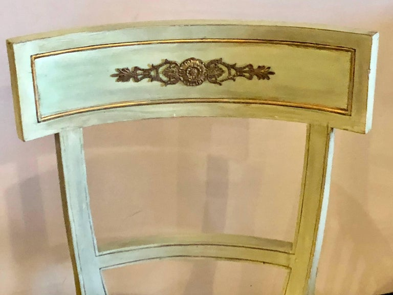 Pair of Hollywood Regency painted with bronze-mounted side or office chairs. In a nice sage green color with bronze mounts and black seat cushions come this decorative pair of wide and impressive side chairs.