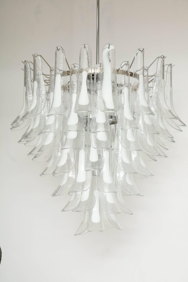 Vintage Vesoi-Italy chandelier composed of three tiers of clear and white Murano glass made circa 1980s. The chome/metal frame has 7 lights (40 watt max each) and is rewired to US standards. This piece is signed (Image 10): Vesoi-Italy.
