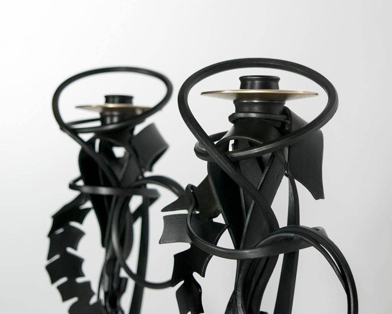 Contemporary American metal sculptor Albert Paley's pair of double shear candleholders are made of formed and fabricated blackened steel and bronze bobeches. All the candleholders in each series are stamped, dated and numbered on the base.