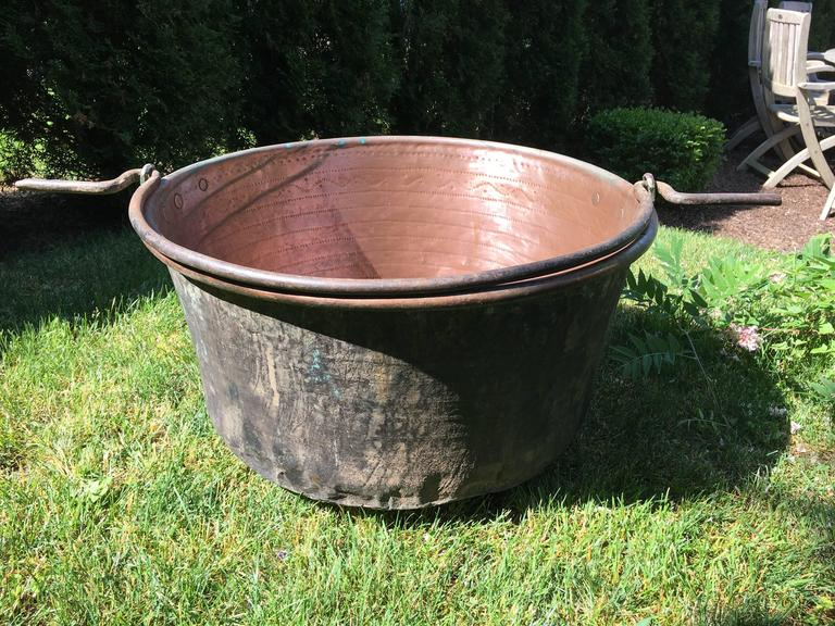 What a beauty! This large handmade copper cauldron has a thick iron handle that extends on either side and the inside has been polished to a brilliant finish. All hand-chased on the interior with exquisite detail, we have left the original dark