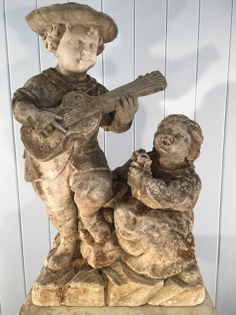 What a charming piece and quite rare! This beautifully-carved statue is most probably from the Low Countries (Netherlands, Belgium, Luxembourg) and features a young boy with mandolin serenading his little sister. She gazes upwards adoringly at him,