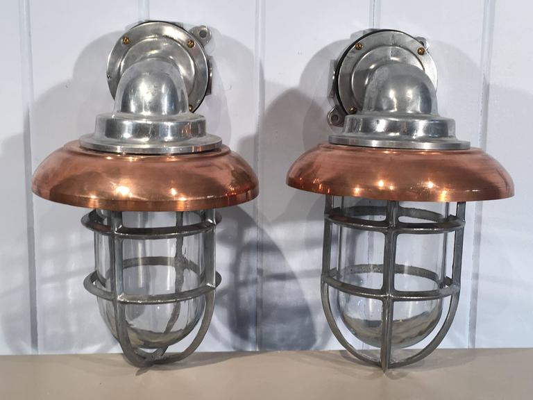 These polished aluminum ship's lamps have been completely restored and now sport removeable replacement copper shades. Their clean Industrial Design mixes well with a multitude of styles and they can be mounted indoors or out. Perfect in a bathroom
