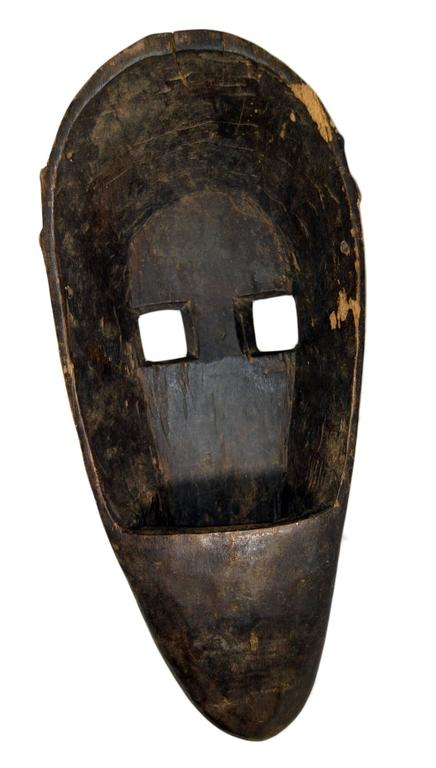 Antique indonesian hand carved dark wood tall mask from