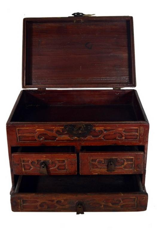 A mid-20th century Chinese jewelry box featuring carved and lacquered drawers. This small rectangular box displays a large bottom drawer and two smaller drawers with carved flat bell-shaped handles. The top opens thanks to a carved hardware lock and
