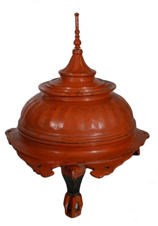 A 19th century Burmese offering basket made of carved wood painted red. This round basket displays a three-legged base with detailed carvings on the edge. The lid adopts a Burmese temple shape, with a sharp top surmounting a gadroon dome. The whole