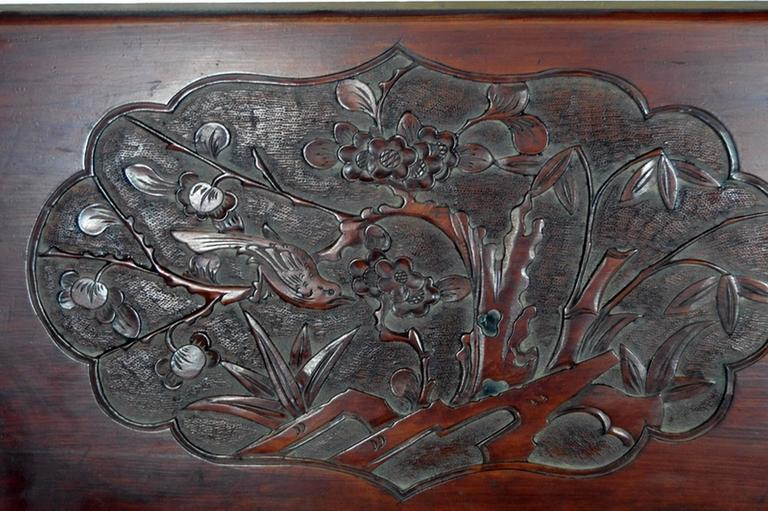 A 19th century Chinese wall plaque hand-carved in lacquered rosewood. This large rectangular wall plaque displays a lobed medallion on its centre. The hand carved frame showcases an enjoyable flower and bird scene, a common and auspicious pattern in