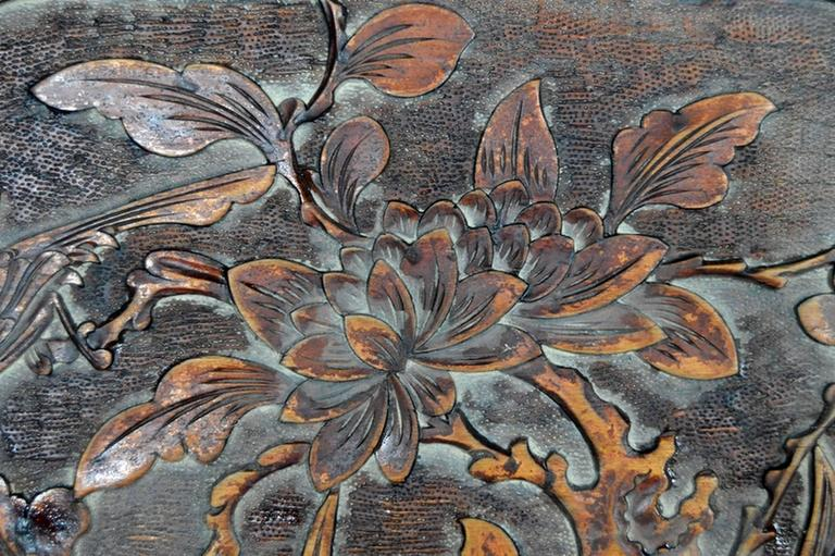 A 19th century lacquered Chinese wall plaque hand-carved in rosewood. This rectangular plaque displays a lobed medallion showcasing a bird and foliage composition. This lightly hand-carved pattern features a bird on the left against a backdrop of