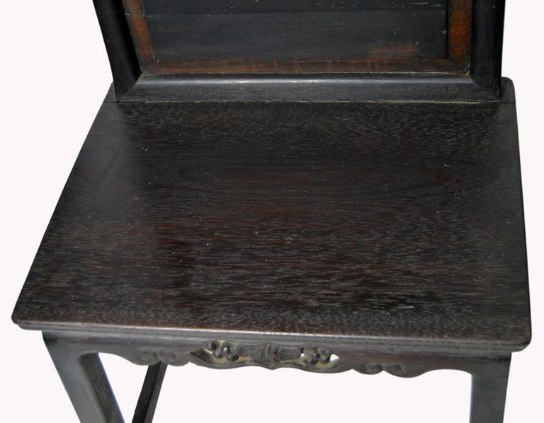 A Chinese Yumu wood side chair from the 19th century, with dark lacquered finish and hand-carved skirt. This Chinese accent side chair features a rectangular molded back topped with a sinuous rail and accented with a central raised panel following