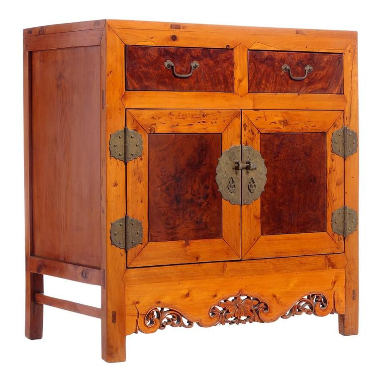 This Chinese side cabinet from the turn of the century (19th-20th century) features two drawers over two doors and is made of elm with burl wood panels on its front. The skirt is nicely adorned with pierced motifs made of a central flower and