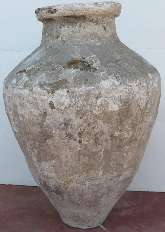 18th century terracotta oil jar with great white stucco patina.