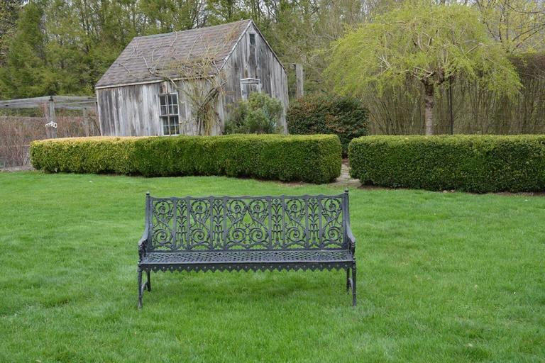 An unusual cast-iron curtain-style garden bench with scalloped and beaded apron, leafy scrollwork, stylized floral elements, and simplified Gothic motifs, American, circa 1900. Measure: 34.75 ins. high, 63.75 ins. wide, 20.5 ins. deep. This pattern