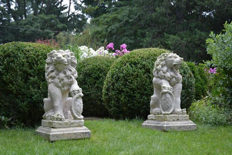 A pair of carved stone gate pier seated lions, looking in opposing directions, each fully-maned beast with one paw raised on a heraldic shield, Bavaria, early 19th century. Measures: Lions 36 ins high, self-bases 5 ins high, 17.5 ins wide, 21 ins