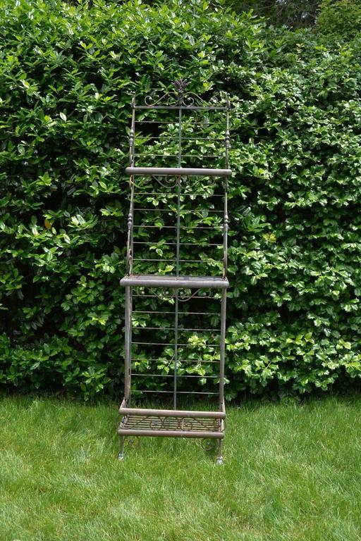 A three-tier wrought iron baker's rack with decorative brass elements, French, circa 1950. Measures: 82.5 ins. high, 22.5 ins. wide, 15.75 ins. deep.