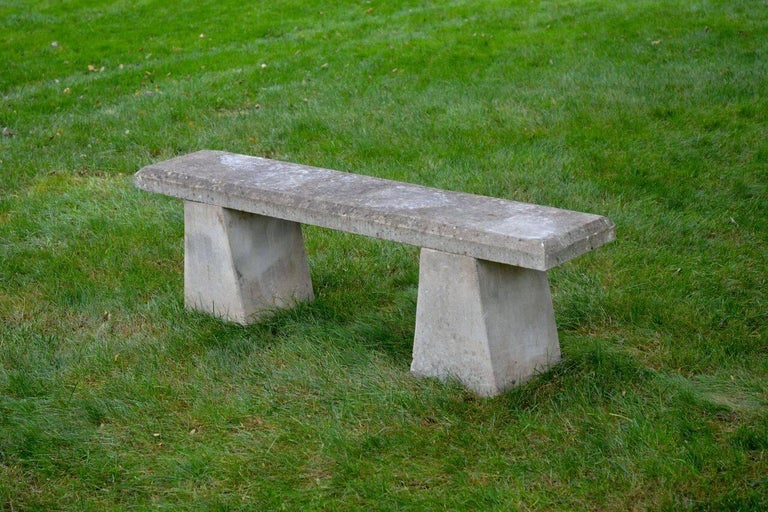 A carved stone bench with simple chamfered slab top, with tapered block supports, English, circa 1950.