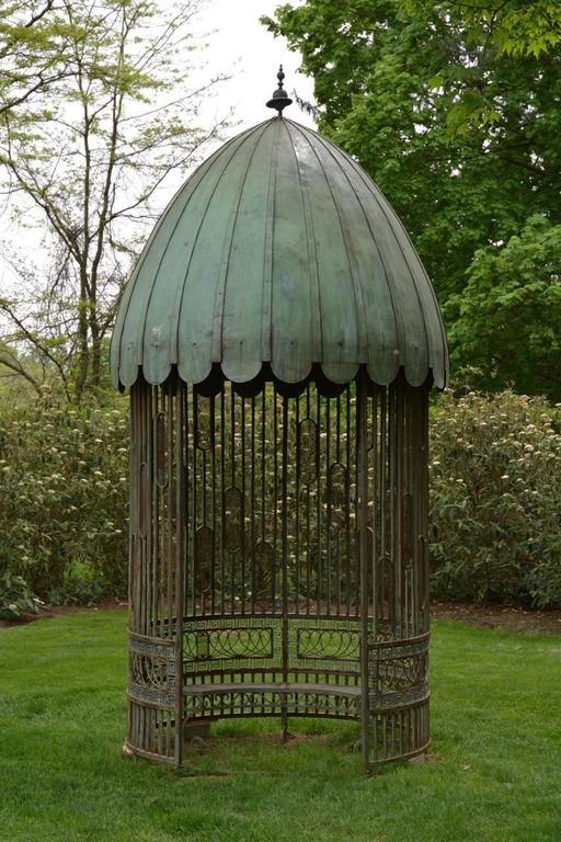 An unusual wrought iron garden pavilion with domed, scalloped copper sheet roof and vertical uprights above a wide band of looped iron and Greek key border with semi-circular interior bench, interior dome fitted with ancient-style oil lamp.