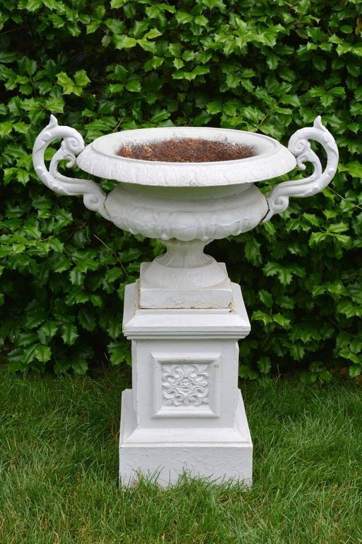A Pair of White Painted Cast-Iron Urns on Pedestals In Good Condition For Sale In Katonah, NY